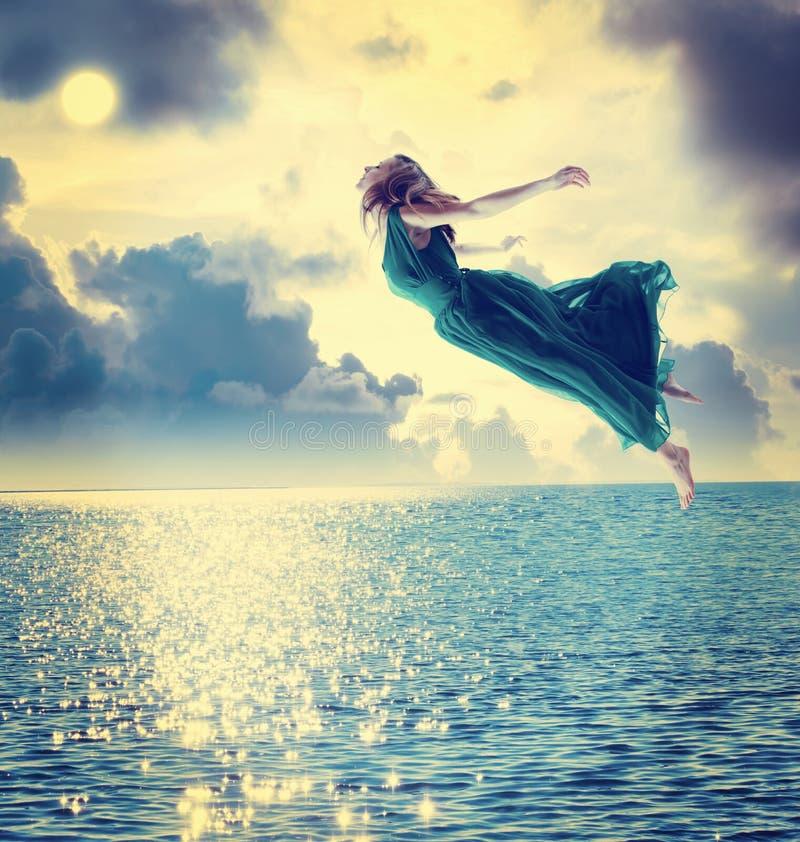 Schönes Mädchen, das in den nächtlichen Himmel springt lizenzfreie stockbilder