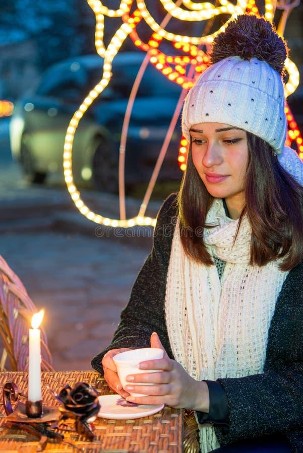Schönes Mädchen, das draußen im Winter mit einer Schale und einem candl sitzt stockbilder