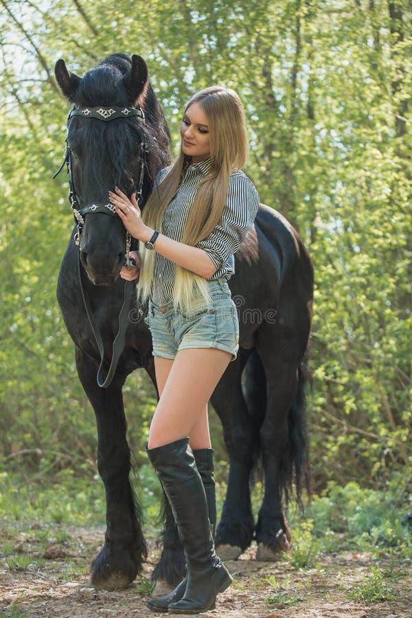 Schönes Mädchen, das draußen Pferd streicht lizenzfreie stockbilder