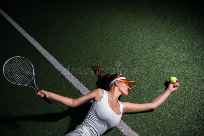 Schönes Mädchen, das draußen Tennis spielt stockbild
