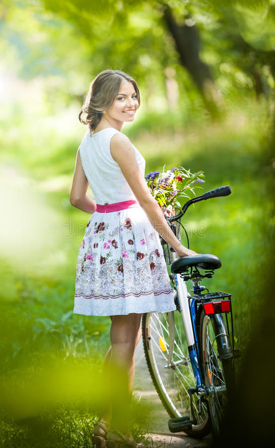 Schönes Mädchen, das ein nettes weißes Kleid hat Spaß im Park mit Fahrrad trägt. Gesundes Lebensstilkonzept im Freien. Weinleselan lizenzfreie stockfotografie
