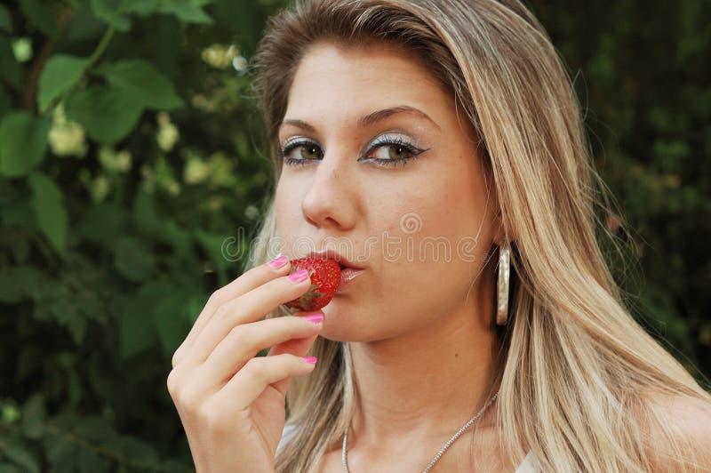 Schönes Mädchen, das eine Erdbeere isst lizenzfreie stockfotografie