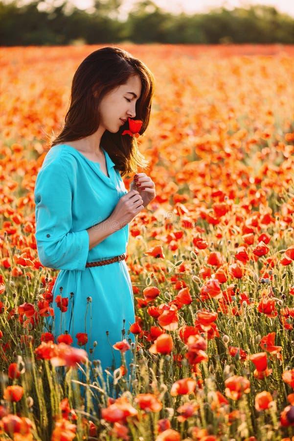 Schönes Mädchen, das eine rote Mohnblumenblume auf dem Gebiet riecht stockfoto