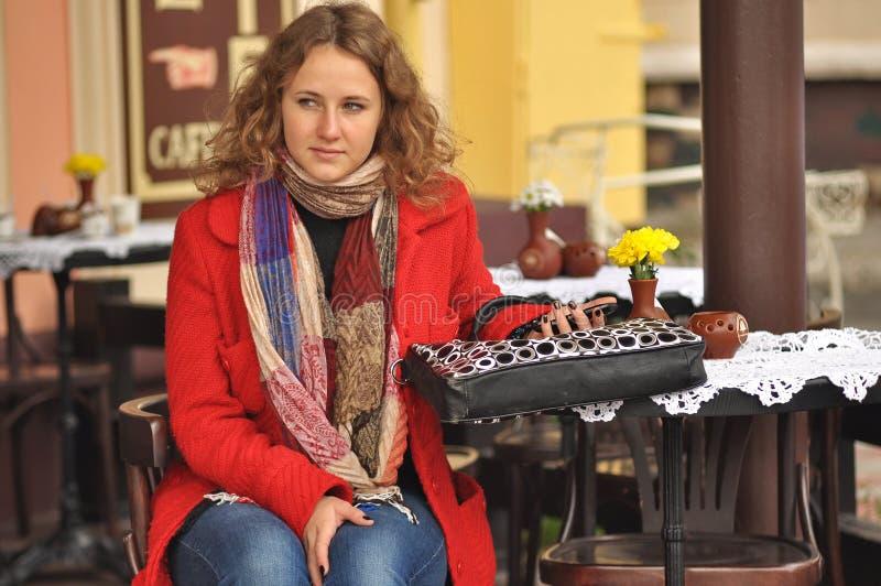Schönes Mädchen, das in einem Café auf der Straße sitzt stockbild