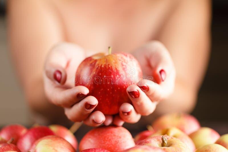 Schönes Mädchen, das einen Apfel in seiner Hand hält Das Mädchen bietet an stockbild