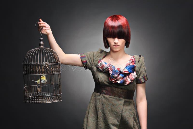Schönes Mädchen, das einen Birdcage anhält stockfoto