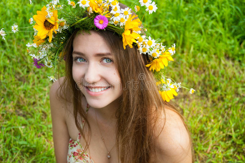 Schönes Mädchen, das einen Kranz von wilden Blumen auf einem Gebiet trägt summe stockbild