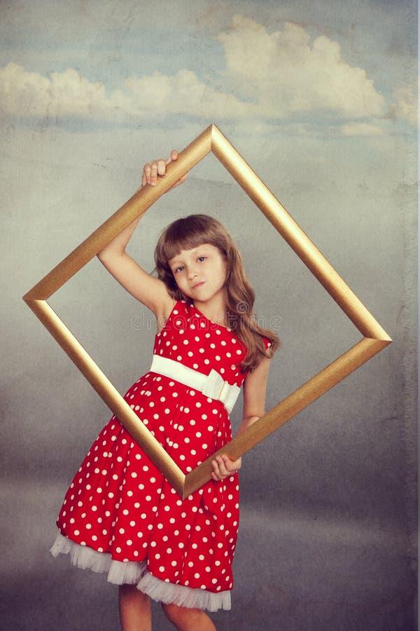 Schönes Mädchen, das einen leeren Rahmen hält lizenzfreies stockfoto