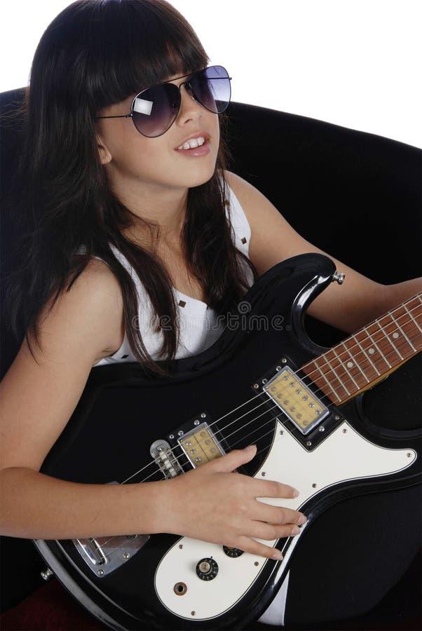 Schönes Mädchen, das elektrische Gitarre spielt lizenzfreie stockfotos