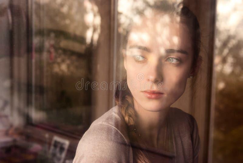Schönes Mädchen, das am Fensterüberwachen steht stockbilder