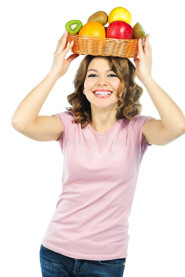 Schönes Mädchen, das frische Früchte über dem Kopf getrennt auf Weiß anhält lizenzfreies stockfoto