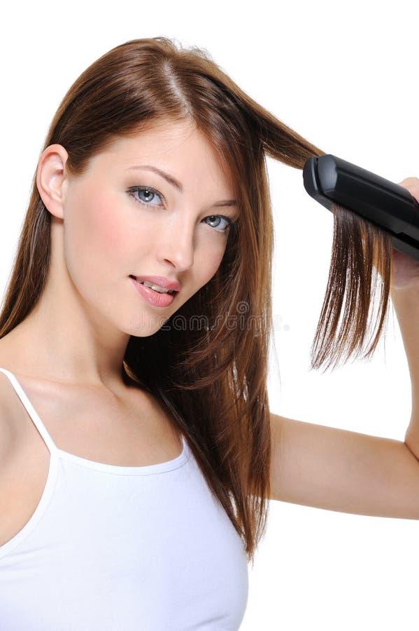 Schönes Mädchen, das Frisur mit Haareisen tut lizenzfreie stockfotografie