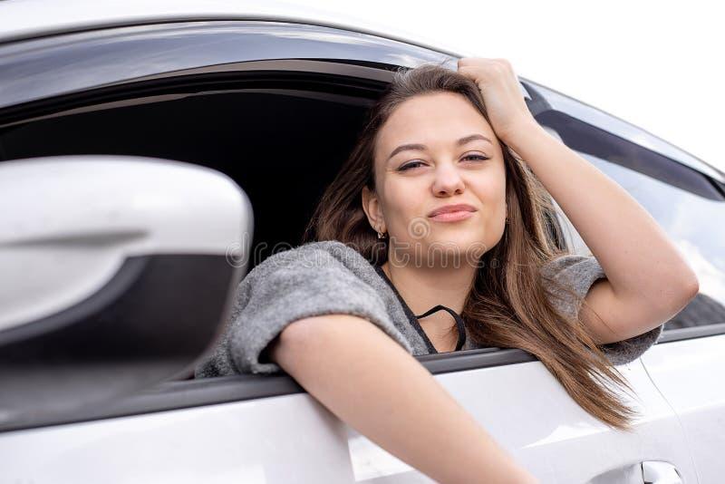 Schönes Mädchen, das heraus in einem weißen Auto und in den Blicken das Fenster sitzt lizenzfreie stockbilder