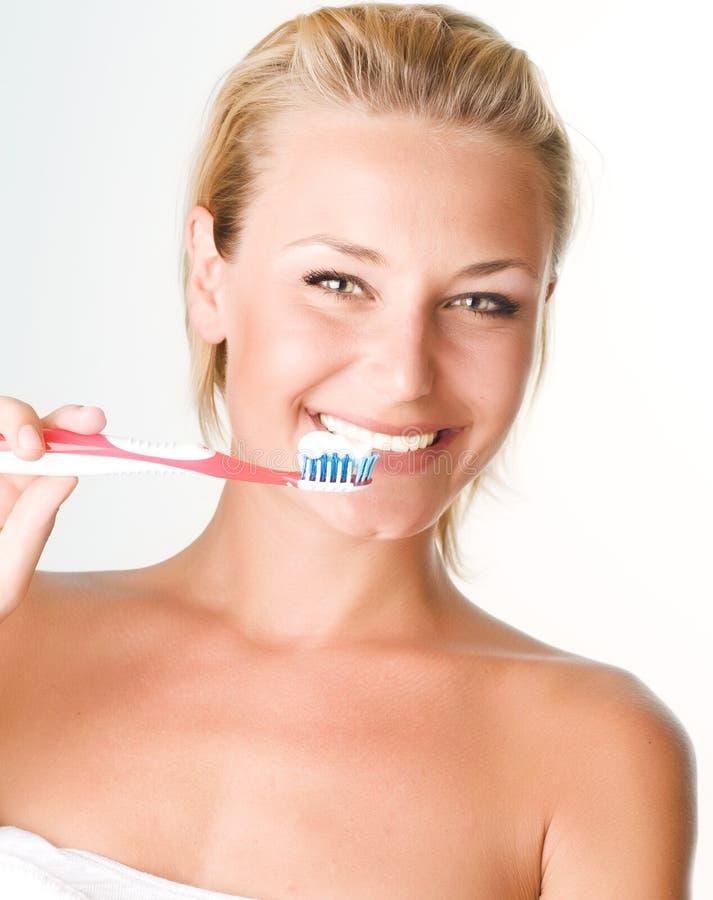 Schönes Mädchen, das ihre Zähne putzt stockfotos