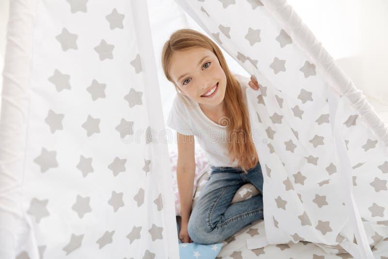 Schönes Mädchen, das in ihrem Schlafzimmer spielt stockfotografie