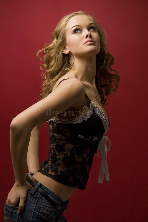 Schönes Mädchen, das im Studio getrennt auf Rot aufwirft lizenzfreie stockbilder