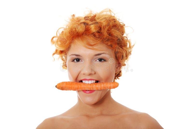 Schönes Mädchen, das Karotte isst stockfotografie