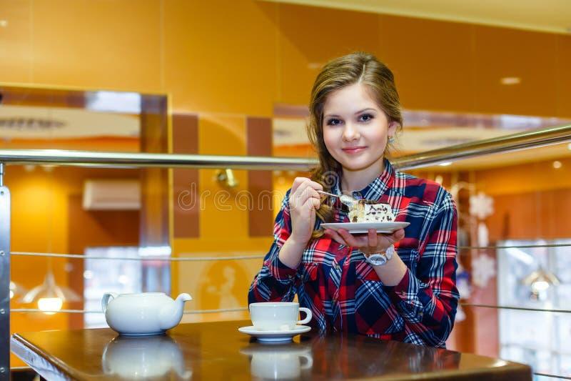 Schönes Mädchen, das Kuchen im Café isst stockbilder