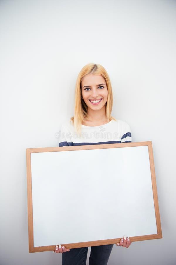 Schönes Mädchen, das leeres Brett hält stockfotografie