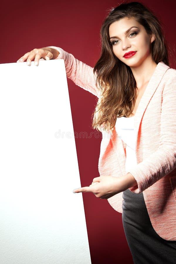 Schönes Mädchen, das leeres Brett zeigt stockfotografie