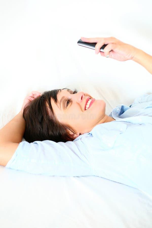 Schönes Mädchen, das liegt Mobiltelefon unten, betrachtend stockfotos