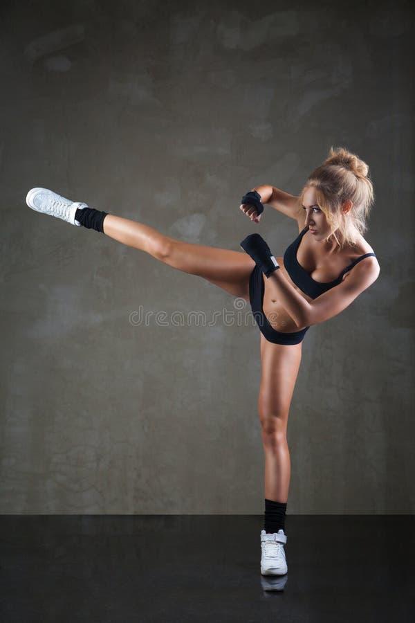 Schönes Mädchen, das mit dem Bein auf dunkelgrauem tritt stockbild
