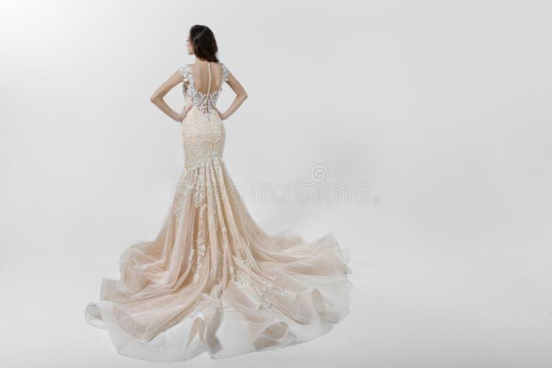 Schönes Mädchen, das mit der Rückseite, gekleidet in einem Heiratskleid mit der Stickerei, lokalisiert auf einem weißen Hintergru stockfotos