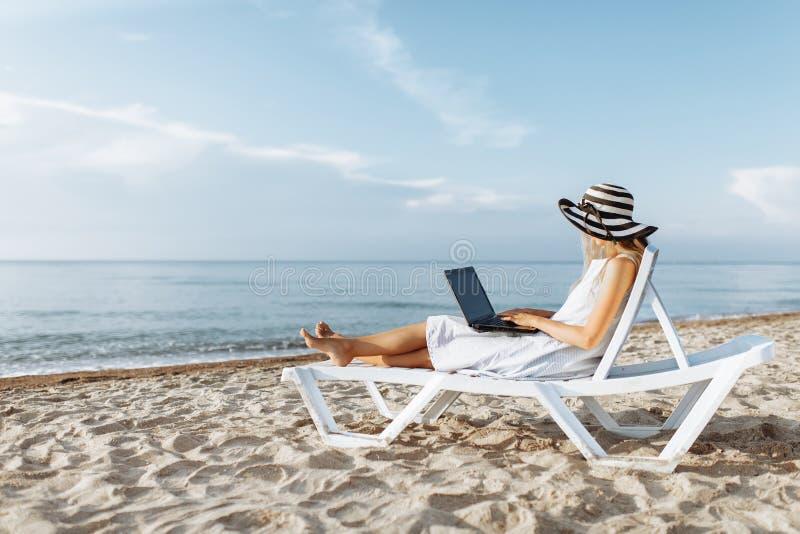 Schönes Mädchen, das mit einem Laptop auf einem Liege, eine Frau im Urlaub arbeitet, Jobsuche sitzt stockfoto