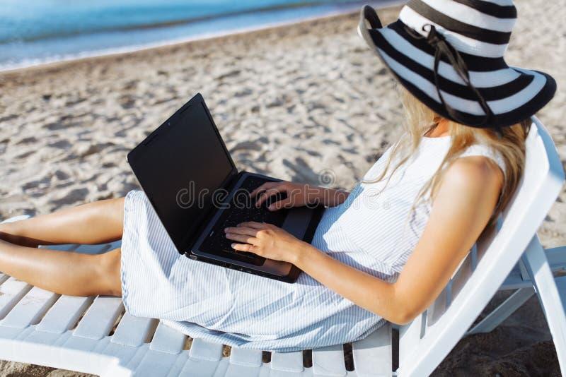 Schönes Mädchen, das mit einem Laptop auf einem Liege, eine Frau im Urlaub arbeitet, Jobsuche sitzt stockfotografie