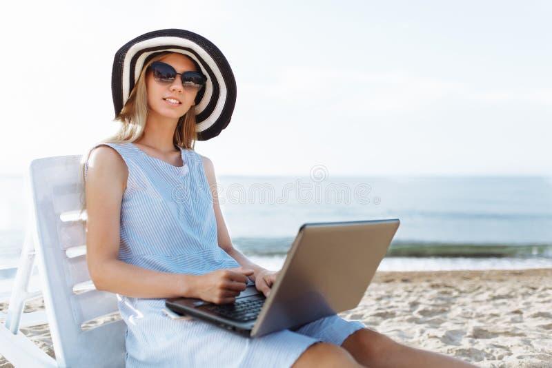 Schönes Mädchen, das mit einem Laptop auf einem Liege, eine Frau im Urlaub arbeitet, Jobsuche sitzt lizenzfreie stockfotos