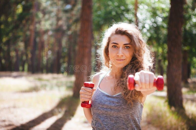 Schönes Mädchen, das mit roten Dummköpfen, Eignungssport im Park trainiert stockbilder