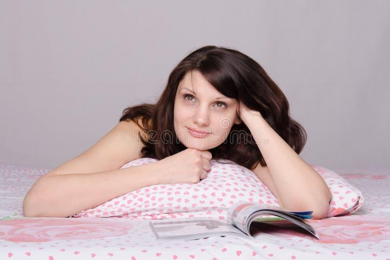 Schönes Mädchen, das nach dem Ablesen eines Artikels in der Zeitschrift träumt lizenzfreie stockfotografie