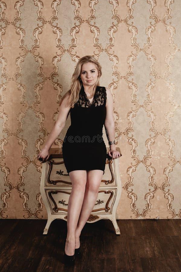 Schönes Mädchen, das nahe dem Weinlese nightstand aufwirft lizenzfreie stockfotos