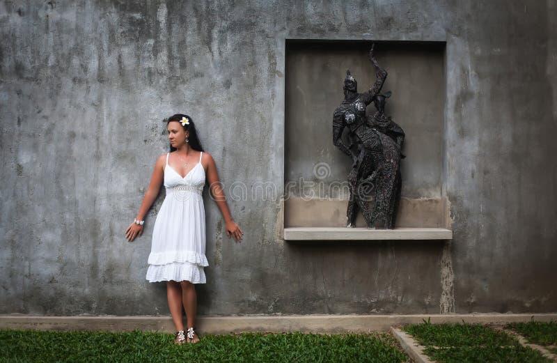 Schönes Mädchen, das nahe der Statue aufwirft eine Frau in einer Dachbodenart Mädchen, das auf Standort aufwirft lizenzfreie stockfotos