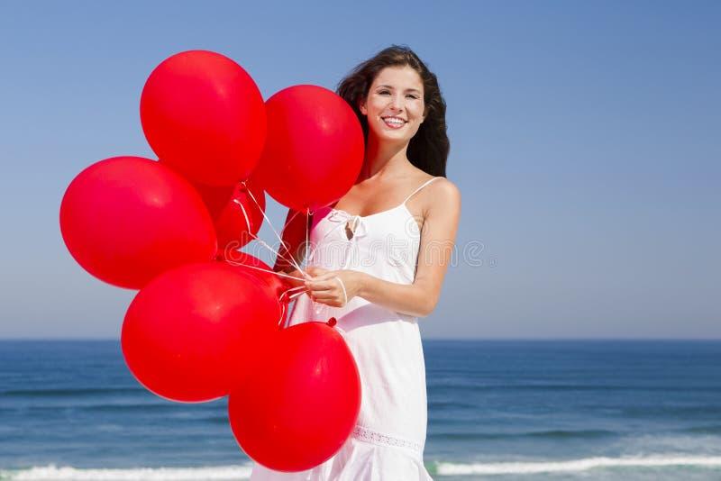 Schönes Mädchen, das rote Ballons anhält stockfoto
