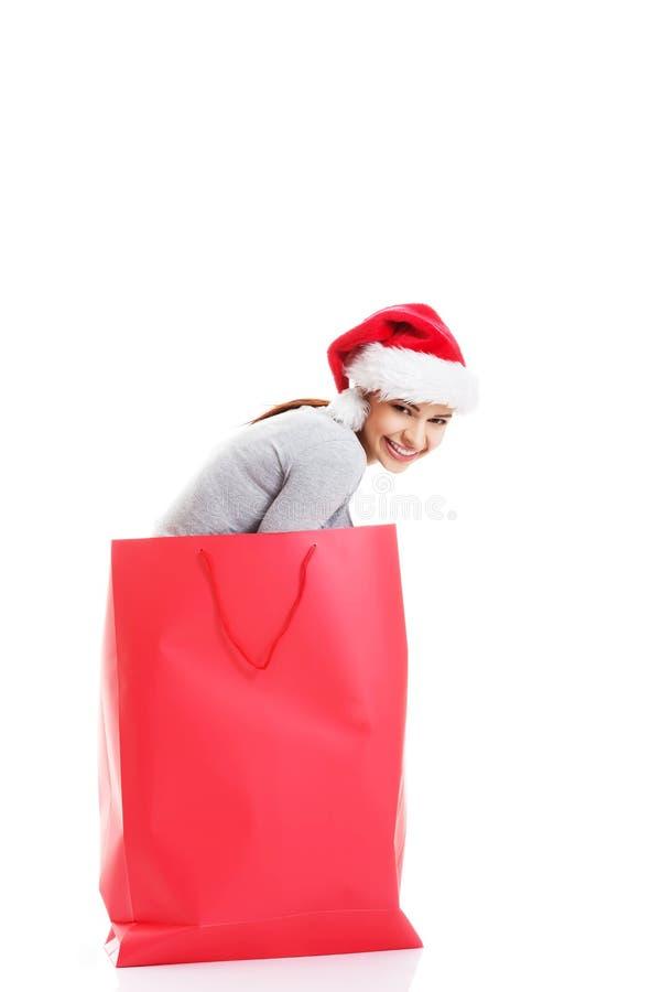 Schönes Mädchen, das Sankt-Hut in der roten Einkaufstasche trägt. lizenzfreie stockbilder