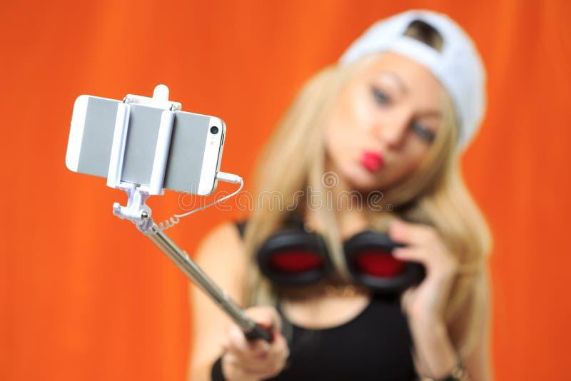 Schönes Mädchen, das selfe Foto am Telefon mit Stock macht stockfoto