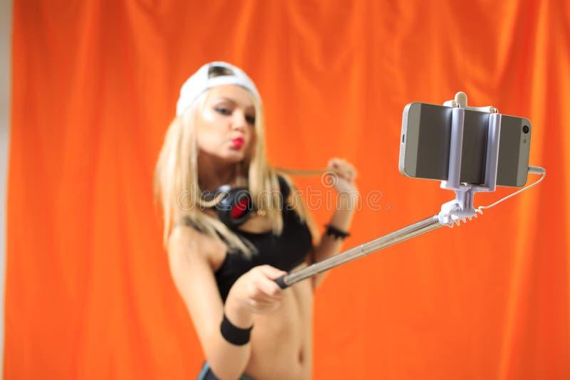 Schönes Mädchen, das selfe Foto am Telefon mit Stock macht lizenzfreie stockfotos