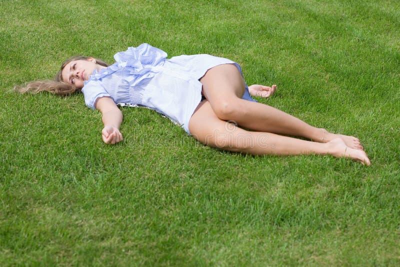 Schönes Mädchen, das sich vom Gras hinlegt lizenzfreie stockfotografie