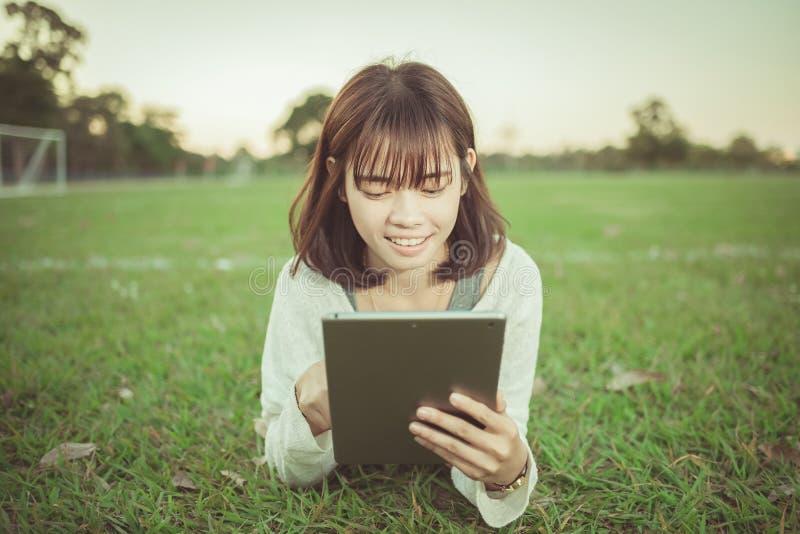 Schönes Mädchen, das Tablette im grünen Park verwendet stockfotos