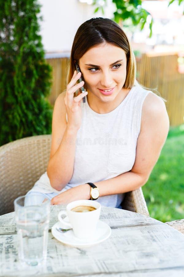Schönes Mädchen, das am Telefon während dinks Kaffee spricht und am Café sitzt stockbild