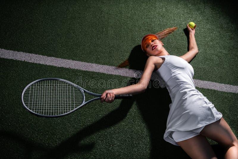 Schönes Mädchen, das Tennis auf dem Gericht spielt stockfoto