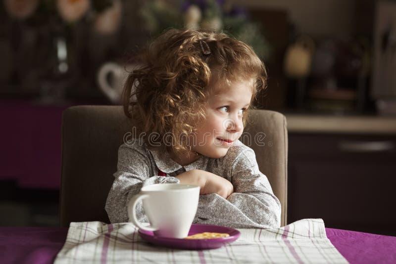 Schönes Mädchen, das am Tisch sitzt lizenzfreie stockfotos