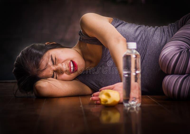 Schönes Mädchen, das unter anorexy leidet, auf den Bretterboden mit ihren Armen um ihr Hauptleiden schreit und legt stockbild