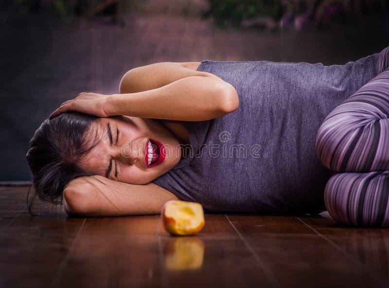 Schönes Mädchen, das unter anorexy leidet, auf den Bretterboden mit ihren Armen um ihr Hauptleiden schreit und legt lizenzfreie stockfotografie