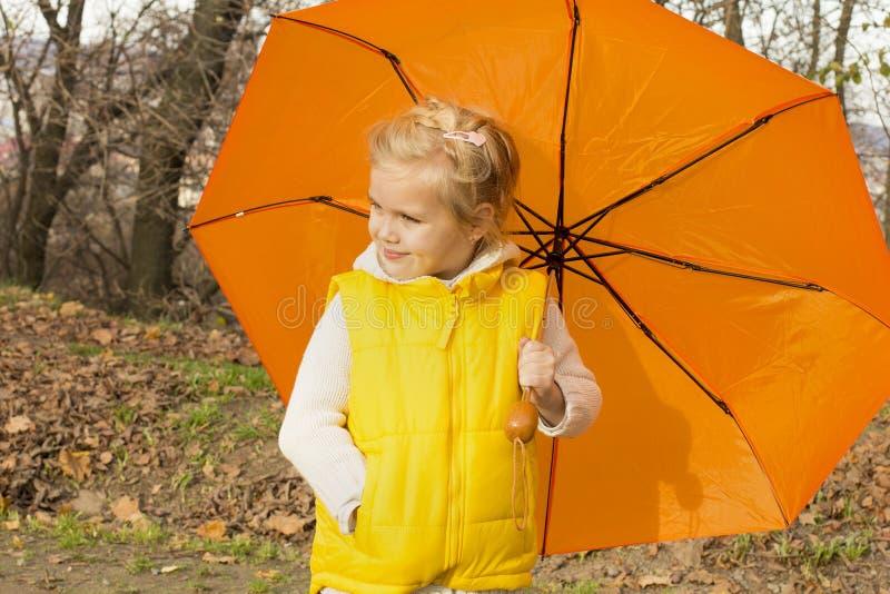 Schönes Mädchen, das unter einem Regenschirm sich versteckt stockfotos