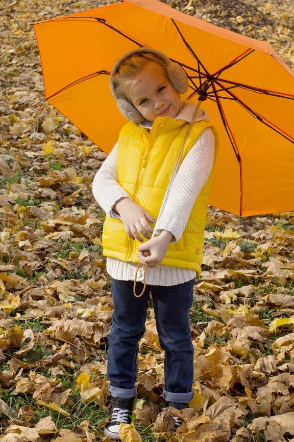 Schönes Mädchen, das unter einem Regenschirm sich versteckt lizenzfreies stockbild