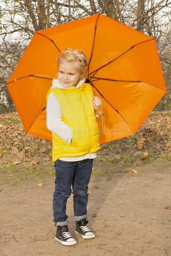 Schönes Mädchen, das unter einem Regenschirm sich versteckt lizenzfreie stockbilder