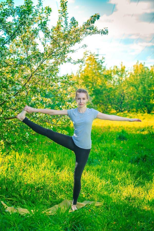 Schönes Mädchen, das Yoga auf Frühlingshintergrund tut stockfoto
