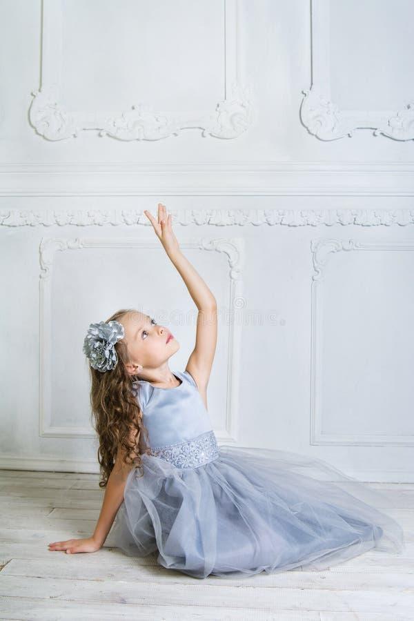 Schönes Mädchen in den grauen Kleider- und pointeschuhen wirft auf dem f auf stockfoto